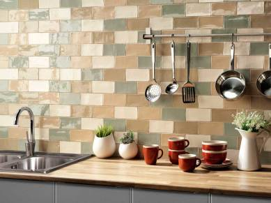 Pared de una cocina con baldosas en tonos verdes y beige con algunos elementos de menaje colgados.