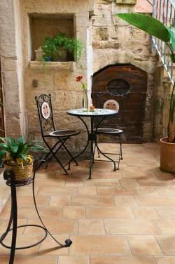 Cerámicas Terradecor-OCCITANIA en jardín pequeño con mesa y dos sillas.