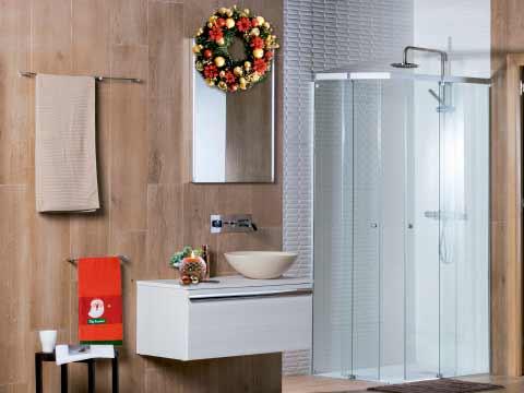 Baño navideño con toalla roja y dibujo de Papa Noel y guirnalda sobre el espejo.