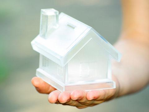 Pérdida de calor donde aparece una mano de mujer sosteniendo una casa de cristal.