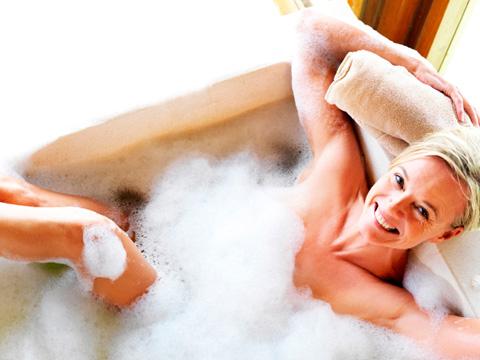 Baño bienestar donde aparece una mujer feliz y sonriente en la bañera.