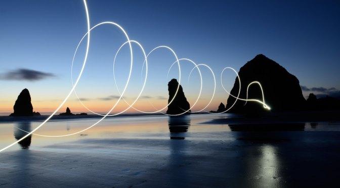 Tramonto sul mare con una scia a spirale bianca che raggiunge uno scoglio
