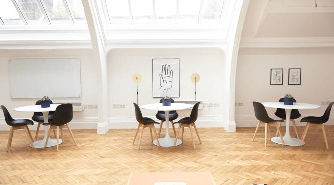 aula che mostra tre tavoli con tre sedie ciascuno