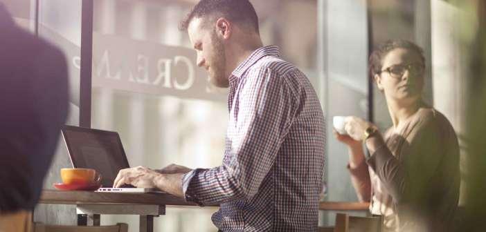 Un ragazzo lavora col proprio laptop in un bar