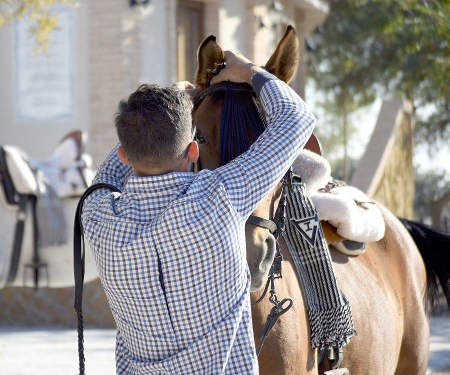 Uno de los vaqueros viste a Pepe, en la finca de la Ganadería San Isidro