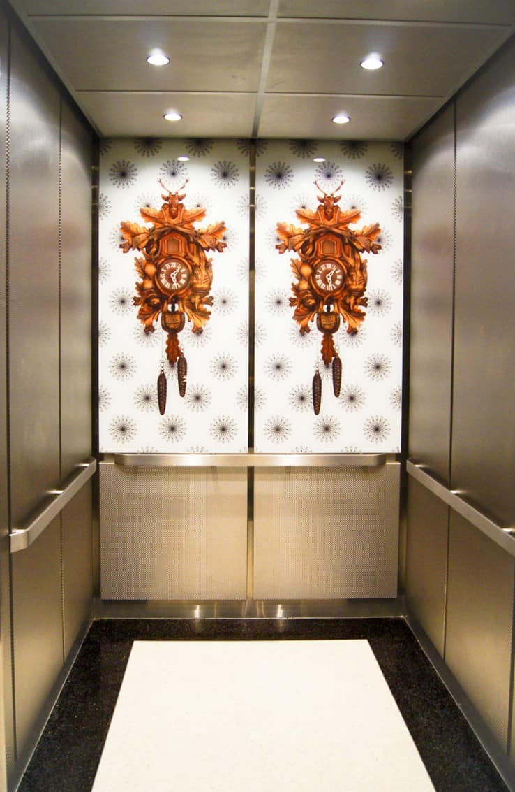 A photo of a custom elevator cab outfitted with patterned stainless steel sidwalls, the rear wall features 2 custom graphics of wood carved cuckoo clocks annealed on an interlayer of white, back-painted safety glass completed in 2013 by G&R Custom Cabs.