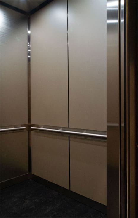 A close up photo of the other sidewall of the same elevator cab with a custom interior at 365 Nicollet, Minneapolis. Materials displayed are laminate, stainless steel and back-painted glass.