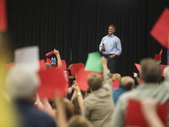 Sen. Jeff Flake smiles as the crowd boos and puts up