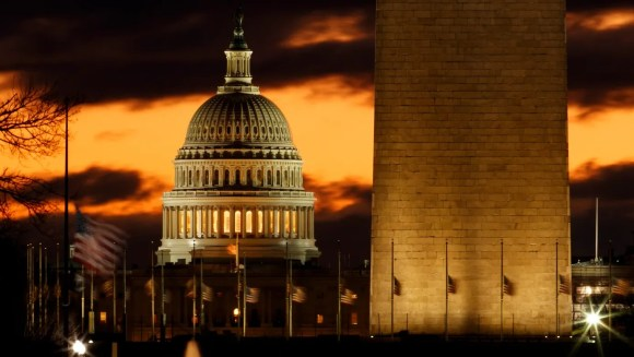 The U.S. Capitol dome is seen past the base of the Washington Monument just before sunrise in Washington. Hundreds of thousands of federal workers faced a partial government shutdown early Saturday after Democrats refused to meet President Donald Trump's demands for $5 billion to start erecting a border wall with Mexico.