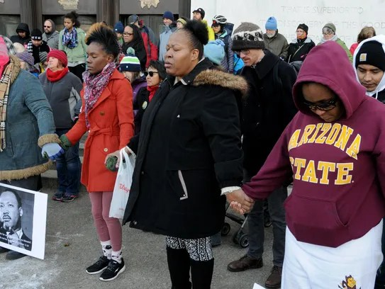 Denise Turner, center, bows her head in prayer following