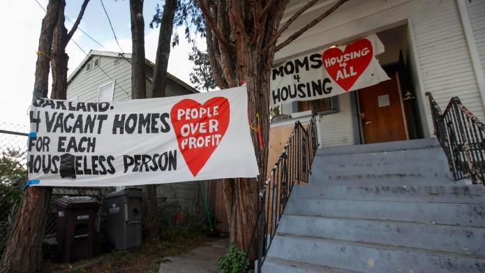 Знаки размещены возле дома, который был занят группой Moms 4 Housing в Окленде, штат Калифорния.