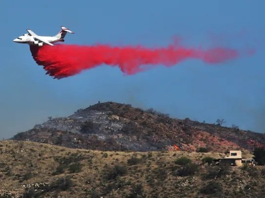 An air tanker drops fire retardant near a hilltop home