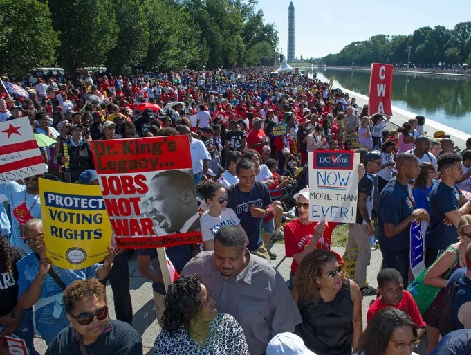 "Thousands of people line the reflecting pool near the Lincoln Memorial while listening to speakers at the 50th anniversary of the March on Washington and Dr. Martin Luther King, Jr.'s ""I have a Dream"" speech in Washington, DC."