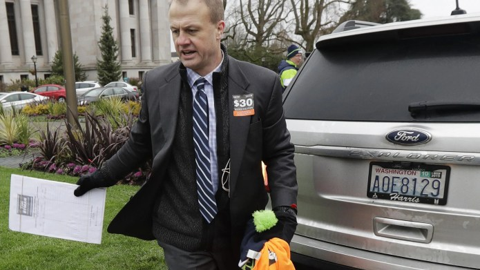 Initiative activist Tim Eyman carries a clipboard as he walks next to his expired car registration tabs before attending a Jan. 13 rally, on the first day of Washington state's 2020 legislative session at the Capitol in Olympia.