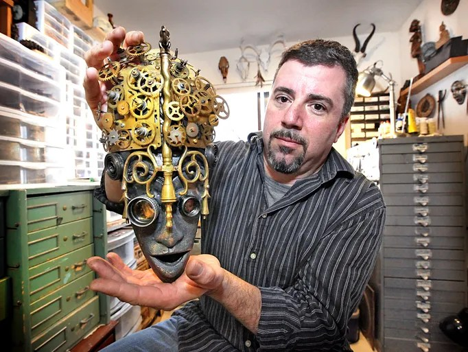 Artist, Larry Agnello of Assemblique. Holding one of his master worked masks made of found and re-purposed items.