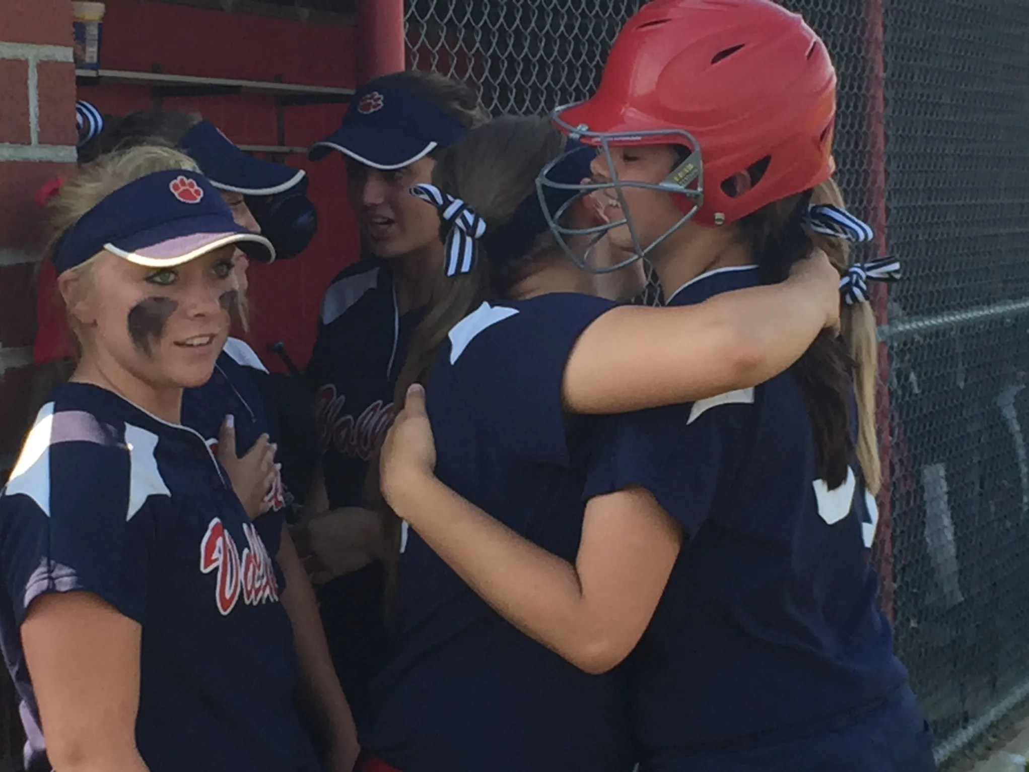 Licking Valley senior Sierra McConnell is hugged by a teammate after  drawing a first-inning