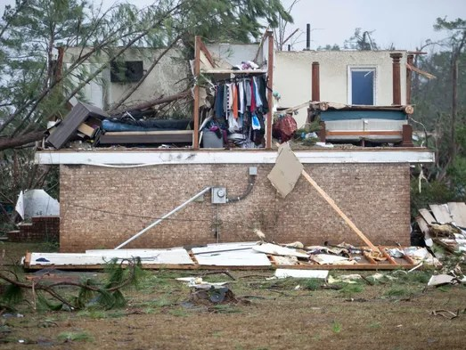 Clothing hangs in the closet of a home where a tornado