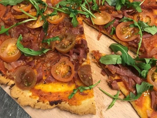 Fresh tomato and arugula gluten-free pizza with prosciutto