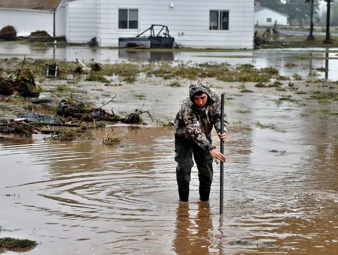 Joey Schendel searches for submerged items while helping neighbors clean their property in a flooded area on Sept. 16 in Hygeine, Colo.