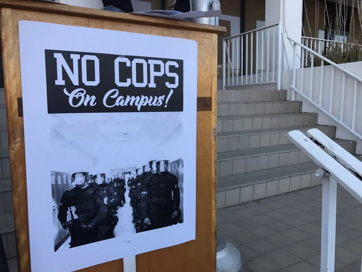 """A """"No Cops on Campus"""" sign on the podium where students"""