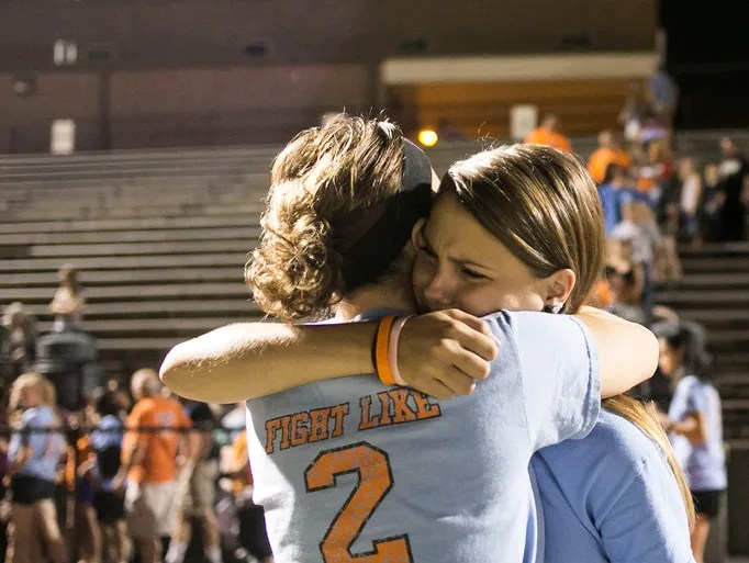 Taylor Kline, 16, right, hugs Amanda Cook after a candlelight