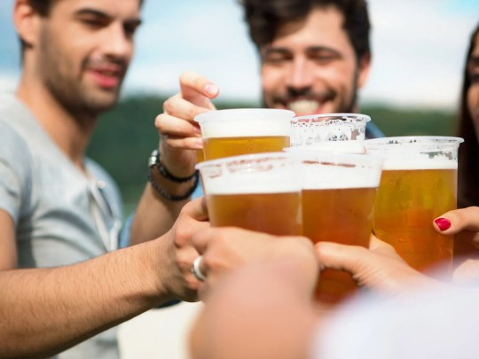 A group of friends toast each other with plastic cups filled with beer.