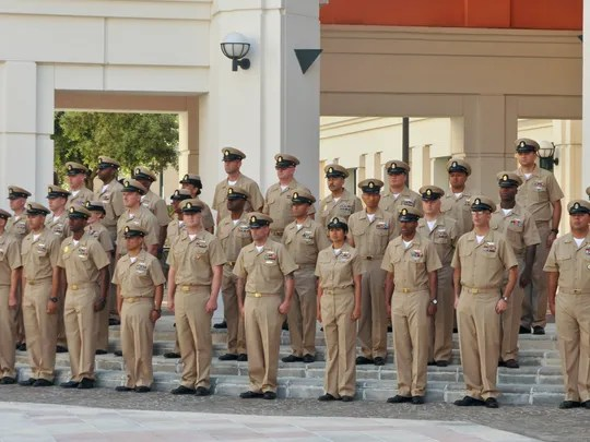 Newly promoted chief petty officers stand at attention