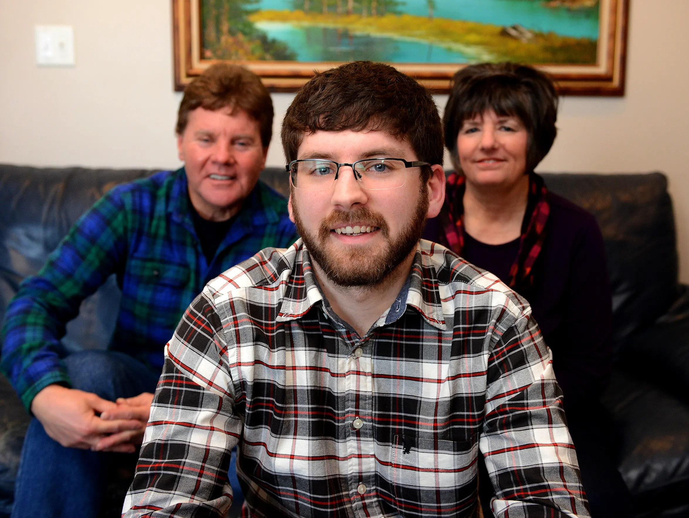 Aaron Emerson, 24, sits with his parents Wes and Rhonda,