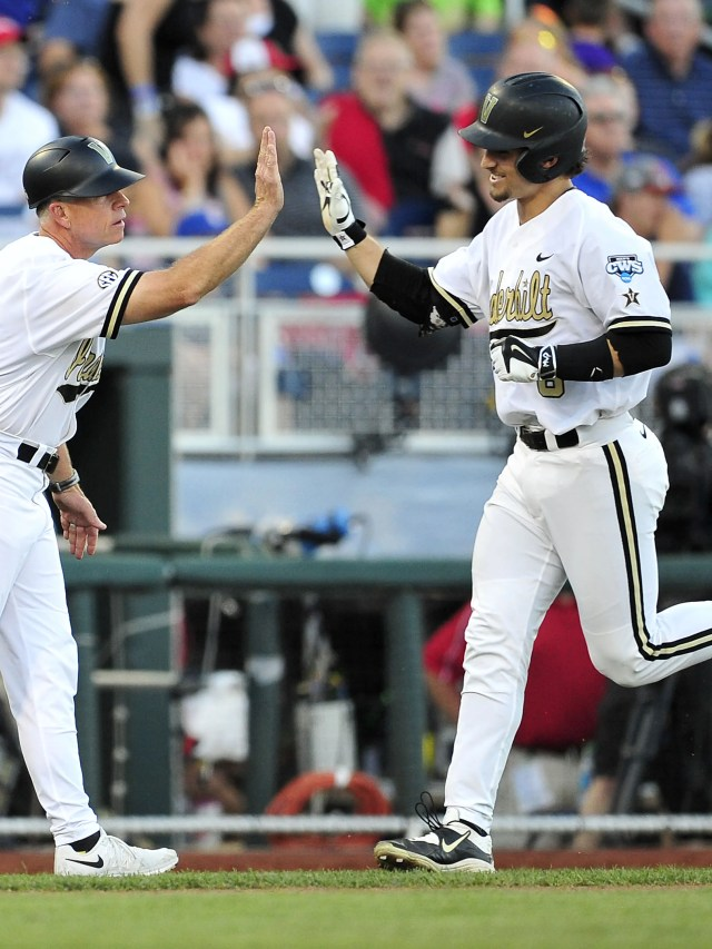 Rhett Wiseman, right, gets a high-five from Head Coach Tim Corbin after hitting a 2-run home run against TCU during the fourth inning in the College World Series at TD Ameritrade Park, Friday, June 19, 2015, in Omaha, Neb.