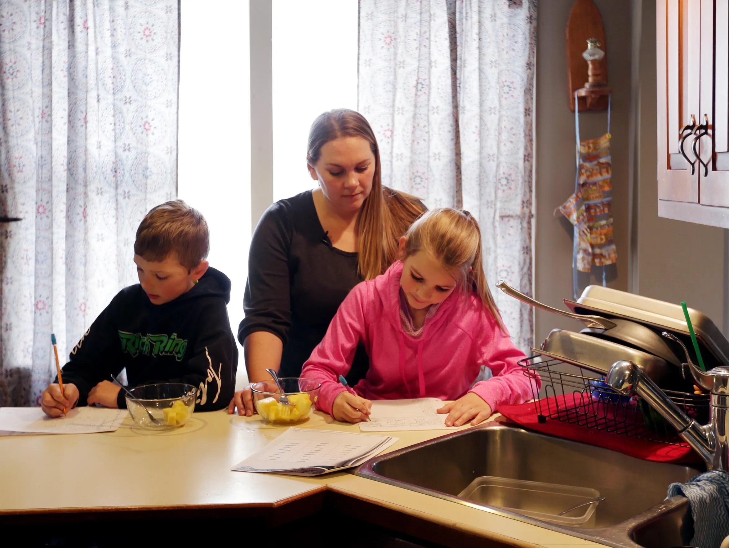 Nicole Rich, 34, helps her children Jamison Rich, 7,