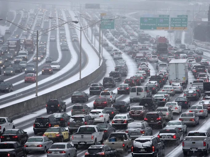 Traffic inches along the connector of Interstates 75 and 85 as snow blankets Atlanta on Jan. 28.