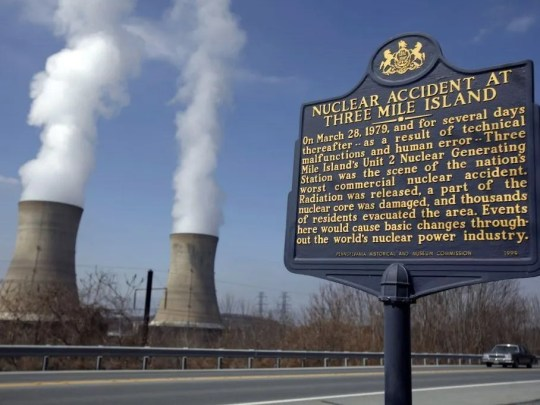 A historic marker is seen as the cooling towers of