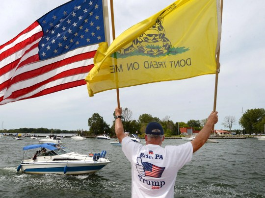 Roger Scarlett of Edinboro greets boaters on the South Pier in Erie during a boat parade in support of President Donald Trump on Sunday. The parade started at the Presque Isle Lighthouse and ended at Dobbins Landing.