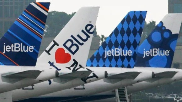 JetBlue planes, each with distinctive tail art, are