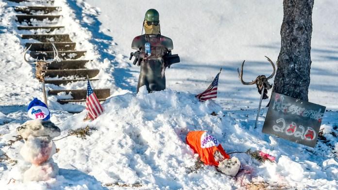 На снежной экспозиции во дворе Дональда Хесселтина в Давенпорте, штат Айова, изображена фигура, застреливающая снеговика в рубашке Берни Сандерса, а другая украшена шляпой Демократической партии.