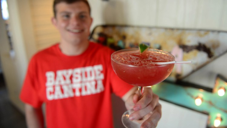 Bayside Cantina's Bartender Robbie Robinson, holds a Jalapeño Watermelon Margarita during the opening of the new restaurant on Tuesday, May 1, 2018.