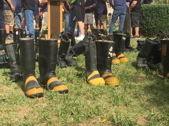 Numerous pairs of boots were placed on the ground at