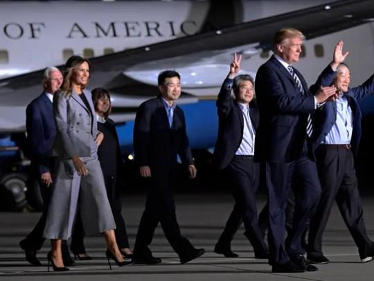 President Donald Trump walks with Tony Kim, fourth