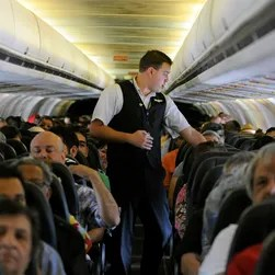 An Allegiant Air attendant helps prepare passengers for
