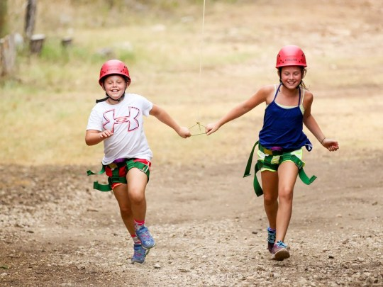 Two campers run together after finishing a ropes course