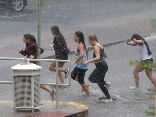 Young women get drenched as they race through the rain