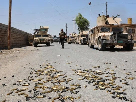 Shell casings lie on the ground as Iraqi government