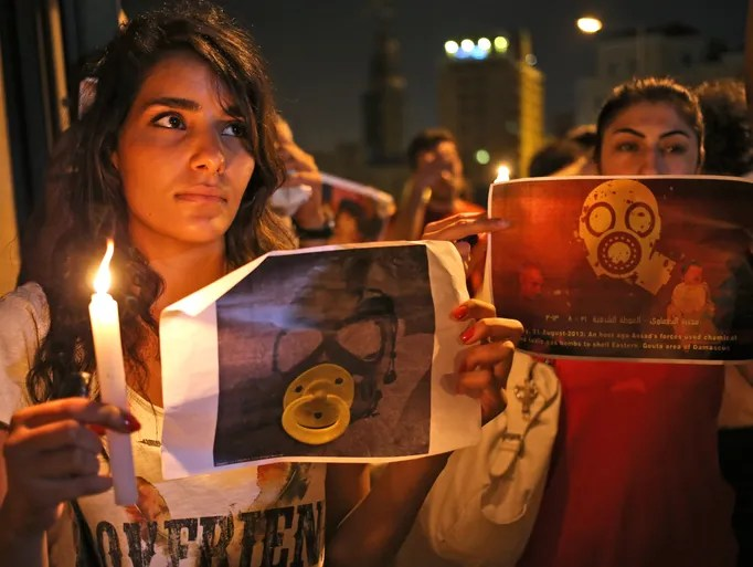 Syrian women, who live in Beirut, hold candles and placards during a vigil against the alleged chemical weapons attack on the suburbs of  Damascus, in front of the United Nations<br /><br /><br />  headquarters in Beirut.