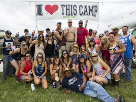 Festival-goers pose for a picture in front of a campsite