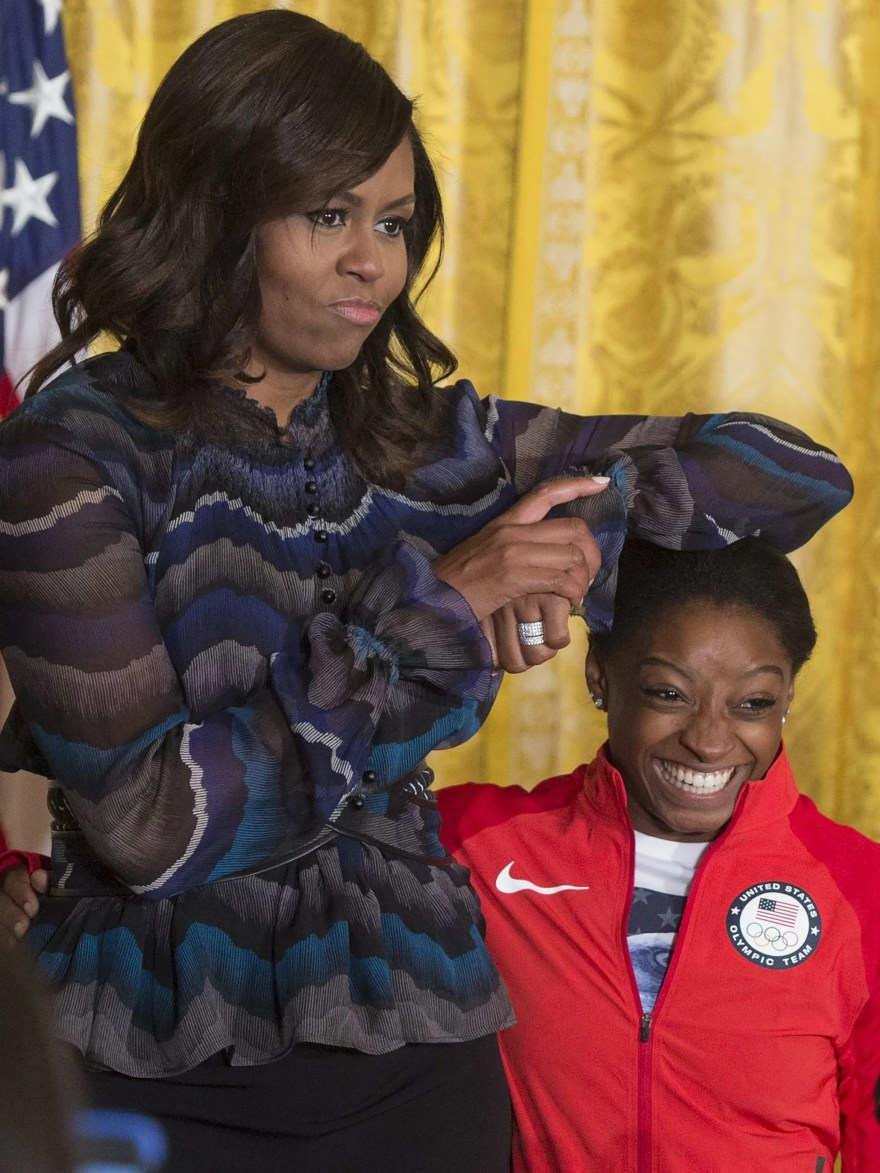 First lady Michelle Obama jokingly uses the head of US Olympics gymnast Simone Biles as an arm rest as they take the stage in the East Room of the White House in Washington during a ceremony where President Barack Obama honored the 2016 United States Summer Olympic and Paralympic Teams.