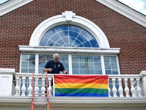 Westwood DPW Superintendent Rick Woods attaches the LGBT Pride flag to the front of Westwood borough hall to begin Pride month on Thursday, June 1, 2017.