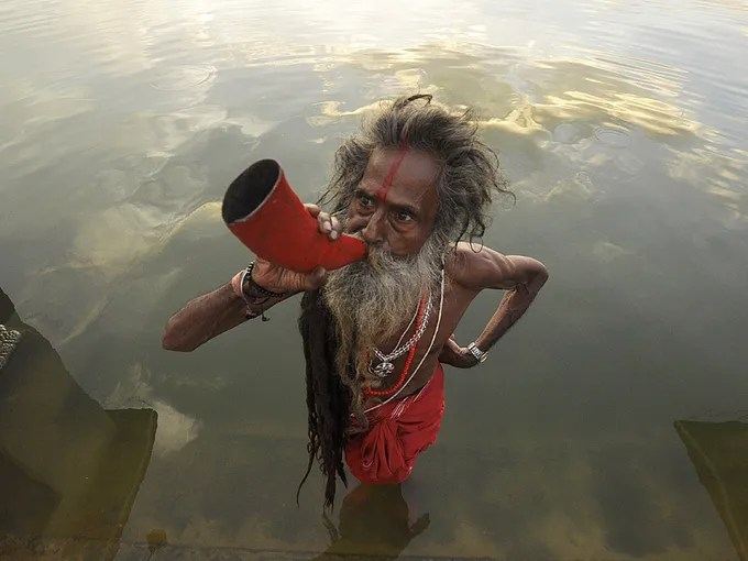 """An Indian """"sadhu,"""" or  """"holy man,"""" blows a buffalo horn on the eve of the traditional Kharchi Puja festival at Agartala.  Kharchi Puja is a week-long festival during which 14 gods are worshiped."""