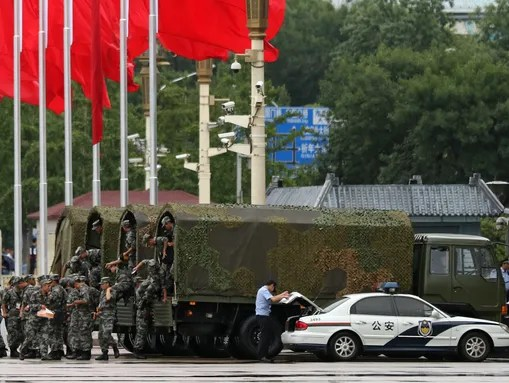 Chinese soldiers get off trucks at Tiananmen Square