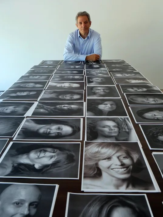Photographer Peter Freed poses in his Rye studio with the black and white portraits he took of women aged 35 to 104 for a book he is working on. (Photo: Joe Larese/The Journal News)