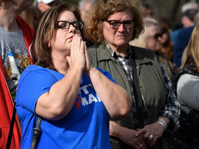 Gretchen Napier holds in hands in prayer during the